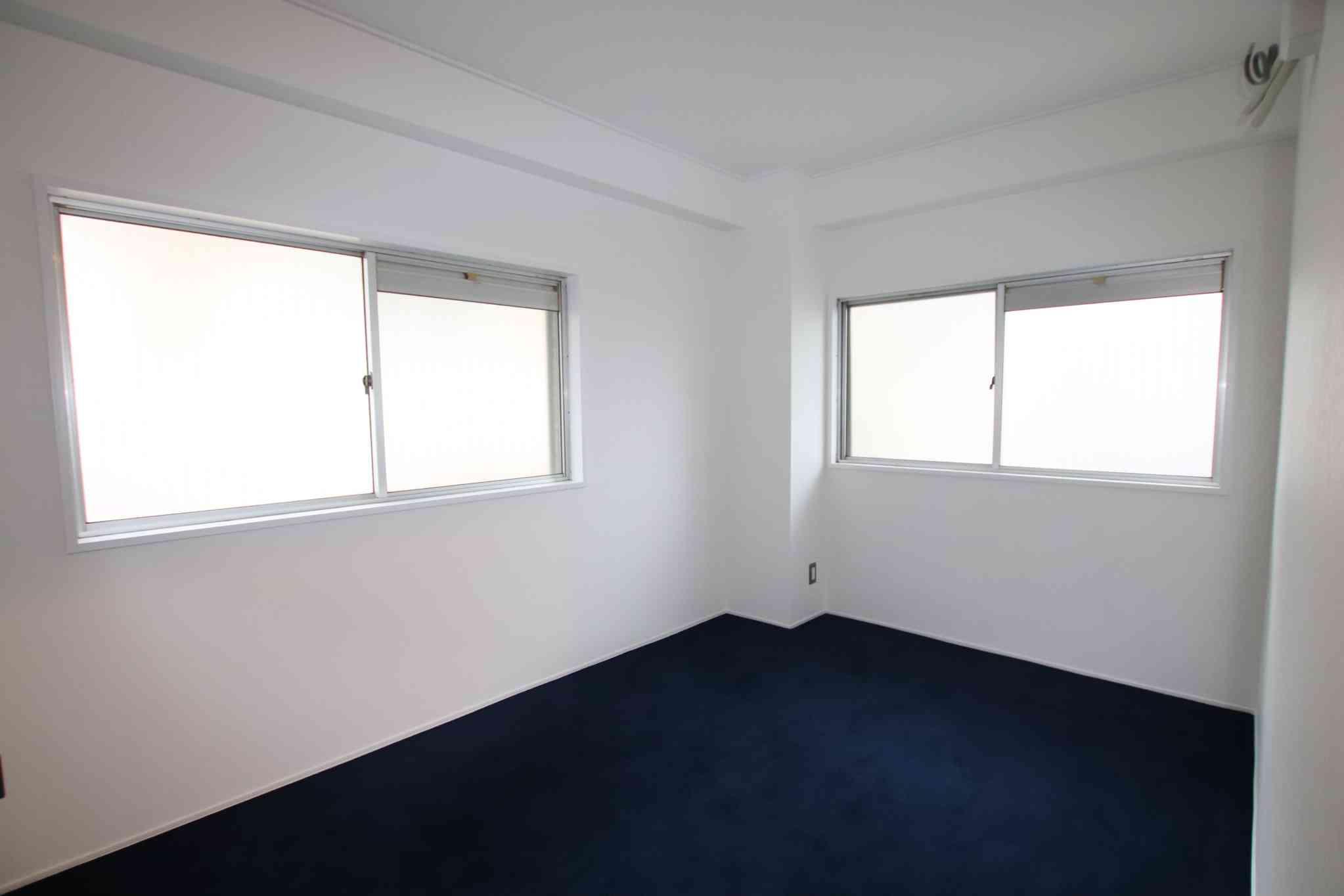 白い壁にネイビーのカーペットが映えるお部屋